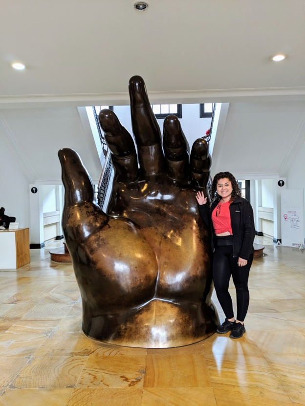 woman posing with giant hand at botero museum